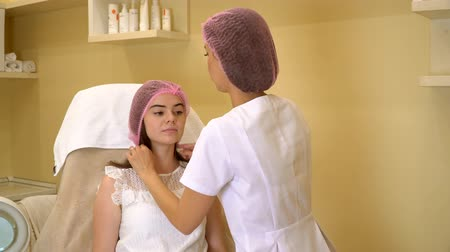 the doctor puts on the patients pink cap. plastic surgery. the patient lies on the bed