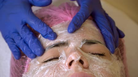 the doctor put a mask from the film on the patients face. spa facilities. plastic surgery. the doctor makes a mask of polyethylene film. close up. Stock Footage