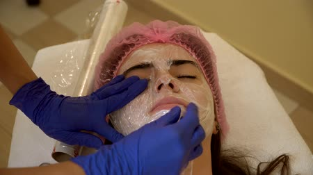 the doctor put a mask from the film on the patients face. spa facilities. plastic surgery. the doctor makes a mask of polyethylene film. close up. Stok Video
