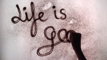 the artist paints the word life is good with sand. sand animation. the inscription on the sand life is good. Stok Video