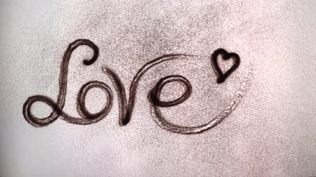 the artist paints the word love with sand. sand animation. the inscription on the sand love.