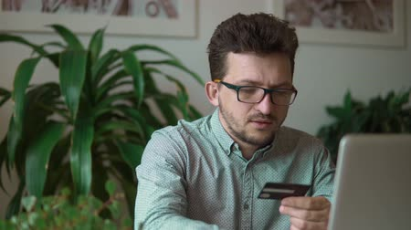 tárcsázás : a young businessman in black glasses and a blue shirt with a credit card in his hands and drives it to the laptop. against the flower and the room. at the office. Stock mozgókép