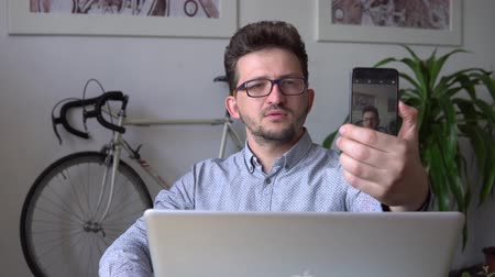 a young guy takes a selfie, sitting at the laptop against the wall with a bike. a young businessman at a laptop makes a selfie. close up. against the bike. in the blue shirt. and black glasses.
