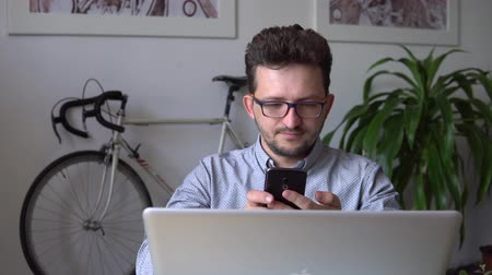 a young businessman takes a selfie, sitting at the laptop against the wall with a bike. close up. against the bike. in the blue shirt. and continues to work.