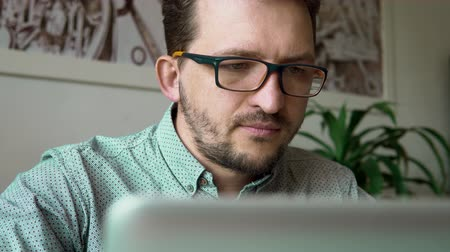 close up. a young businessman sitting at a laptop looking at the screen and working. at the office. against a white wall with pictures and a flower. dressed in a blue shirt and glasses. Stok Video