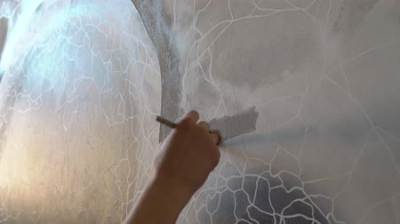 The artist paints a picture with a brush on canvas with gray paint.The hand draws a pattern of gray lines on the painted surface .