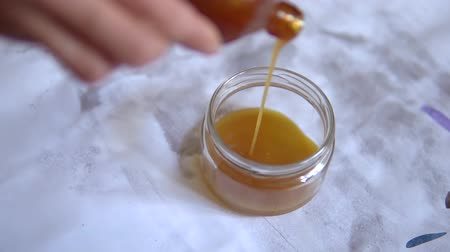 pour the yellow paint varnish into a glass jar. pour the solvent into the jar. poured from the bottle glass jar.