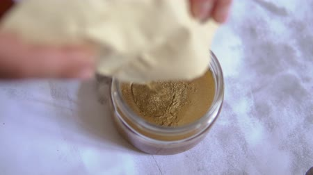 pour the powder bronze paint in a glass jar with varnish. make paint. dissolve the paint. paint dust. Stok Video