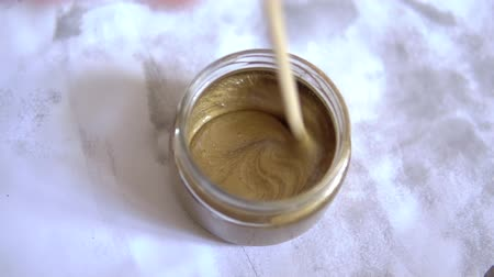 hůlky : hand stir the bronze color paint glass jar. stir the yellow paint. brown paint. on white background.