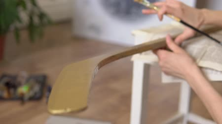 Paint a hockey stick with paint of bronze color. Paint a wooden stick bronze  brown  yellow paint. The Board is varnished with a brush.
