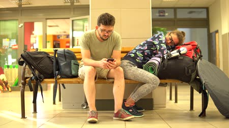türelem : The guy with the girl sitting on a bench with bags. The guy with the girl waiting for the train at the station. The guy looks at the phone , the girl was asleep. Stock mozgókép