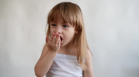 comer : Little girl plays with a cookie and puts it to her mouth
