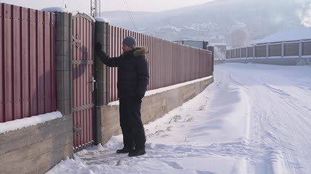fur boots : Young man knocks at the door on a fence
