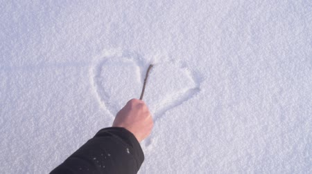иней : Heart is being drawn on the snow by a male hand with a stick.