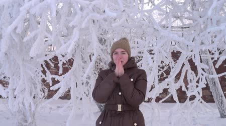 mrazivý : Frozen woman is warming her hands. She is standing under the tree covered with snow.