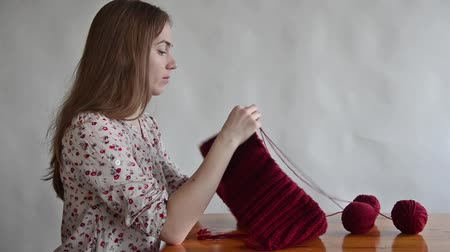 příze : Young woman is sitting at a wooden table and knitting a dark red snood.