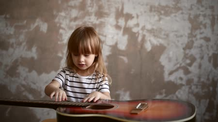 retouched : Little girl is playing with a guitar on a grunge background. Soft focus. Vignette is added.
