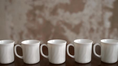 retouched : White tea mugs are placed in a row on a table with a grunge background.