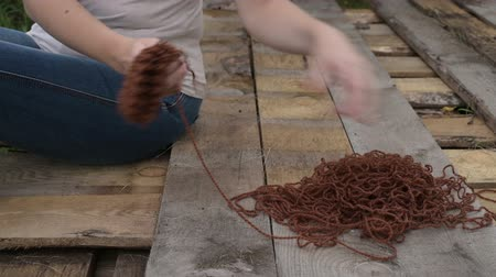 undo : Woman unravelling the knitting outdoors Stock Footage