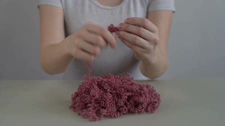 meada : Woman clewing the pink yarn up