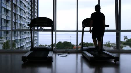 silhouette of female walking on treadmill with beach view Stock Footage