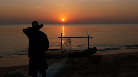 halászok : Silhouette of fisherman fishing net from the boat and collect fishes on the sunset Pattaya beach in Thailand.