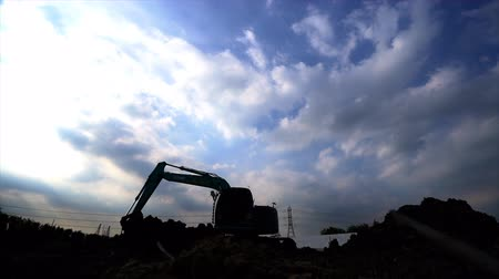 silhouette of digger with sun in construction site