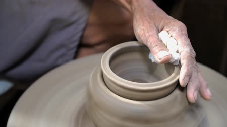 oleiro : Close-up shot of half-finished ceramic vase spinning on potterss wheel and hands molding clay with professional tools