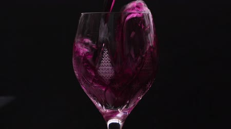 Бордо : Close-up of pouring red wine from bottle into wine glass in super slow motion. Pouring red wine into goblet. Red wine forms beautiful wave in glass. Free space for text. Low key Стоковые видеозаписи