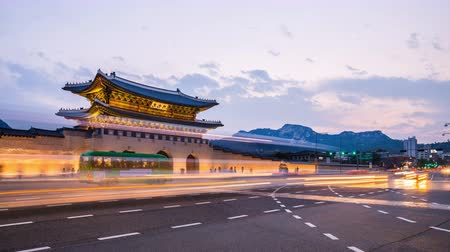gyeongbok : Gyeongbokgung Palace, Cars passing in front of Gwanghwamun gate after sunset in downtown Seoul, South Korea. Name of the Palace Gyeongbokgung Stock Footage