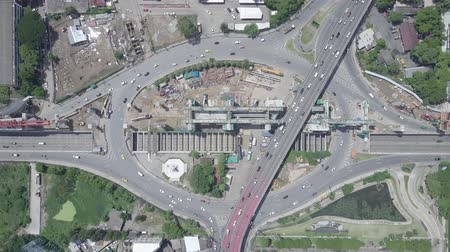 bouwwerf : Aerial top view of public transport electricity train construction in the centre of roundabout and tunnel with cars moving in Bangkok Thailand Stockvideo