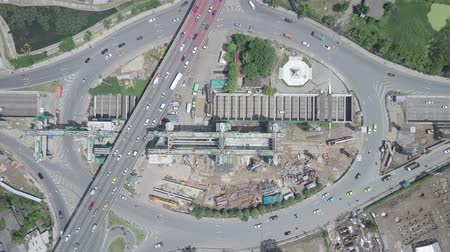 tünel : Aerial top view of public transport electricity train construction in the centre of roundabout and tunnel with cars moving in Bangkok Thailand Stok Video
