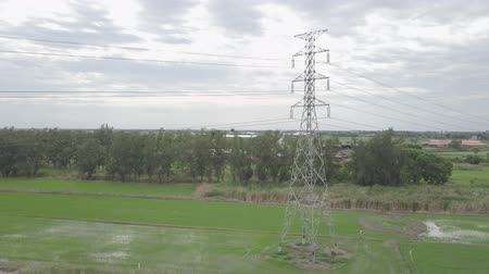 pilon : aerial view moving up of high voltage electricity pylon in farmland Thailand