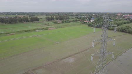 metrópole : aerial view moving down of high voltage electricity pylon in farmland Thailand