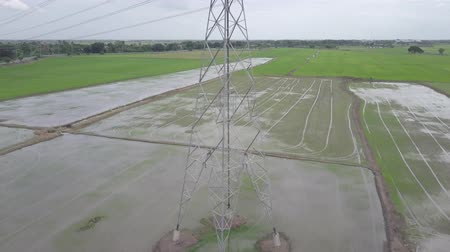 metrópole : aerial view moving up of high voltage electricity pylon in farmland Thailand