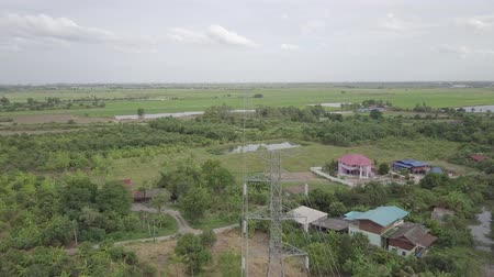 metrópole : aerial view moving over high voltage electricity pylon in farmland Thailand