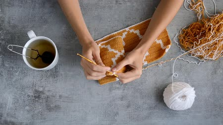 knitted : young womans hands crocheting with orange and white cotton thread on stone table background, top view close-up full HD stock video footage in real-time Stock Footage