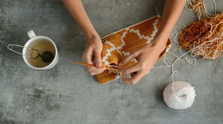 crochê : young womans hands crochet hook with orange and white cotton threads on stone tabletop background, view from above close-up full HD stock video footage in realtime