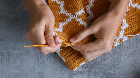 trigo sarraceno : adult girls hands crochet hook with orange and white cotton threads on stone tabletop background, view from above close-up full HD stock video footage in realtime