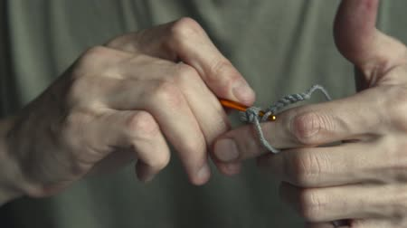 punti maglia : man in green t-shirt begins crocheting with gold hook and gray cotton thread, front view macro full HD stock video footage in real-time Filmati Stock