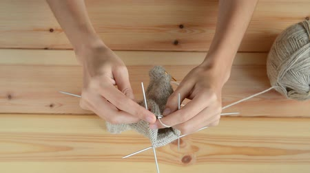 meada : adult girls hands knitting with gray metallic needles and woolen thread on wooden table background, view from above close-up full HD stock video footage in real-time