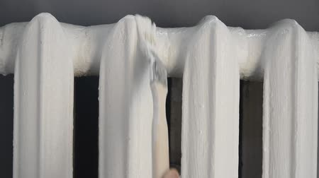mansão : caucasian mans hands painting with paint brush cast-iron battery radiator in white color, close-up full HD stock video footage in real-time