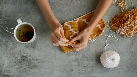 crochê : adult girls hands crocheting with orange and white cotton thread on stone table background, top view close-up full HD stock video footage in real-time