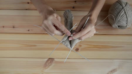 meada : young womans hands knitting with gray metal needles and woolen thread on wooden table background, top view close-up full HD stock video footage in real-time