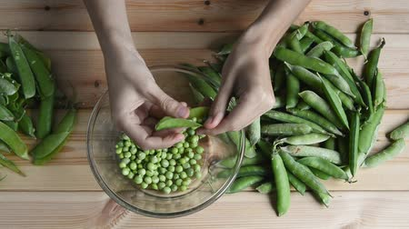 bezelye : womans hand takes and sorting fresh green pea bean from stack, opens and puts peas into glass bowl and husk on wooden table, top view of closeup full hd stock video footage in real time