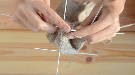 編み物 : young womans hands knitting with gray metal needles and woolen thread on wooden table background, top view close-up full HD stock video footage in real-time