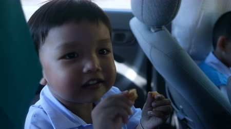 kalmak : Cute boy talking with someone and say good bye while chewing snack inside a car Stok Video