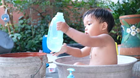Boy pouring water into bucket and stay inside plastic bathtub