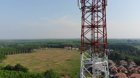 Aerial view on tower. Circling and moving up around antenna transmission with cityscape