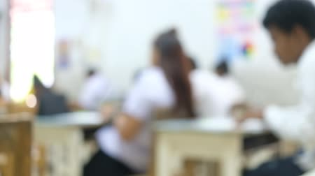 Defocused students testing an examination in the classroom